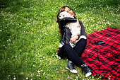 istock young girl with dog on grass with flowers in park 533577562
