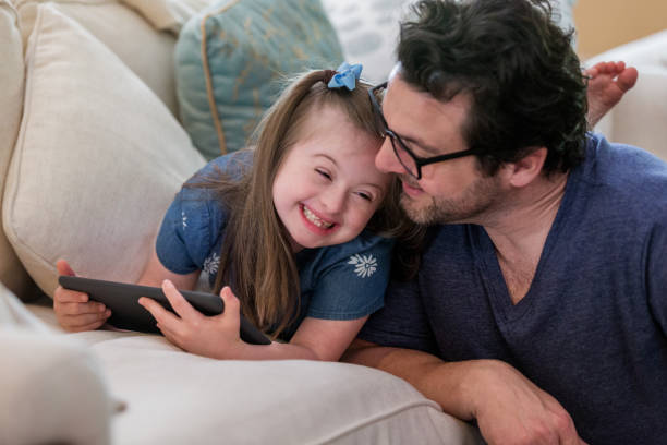 Young girl with Down Syndrome giggles with dad stock photo