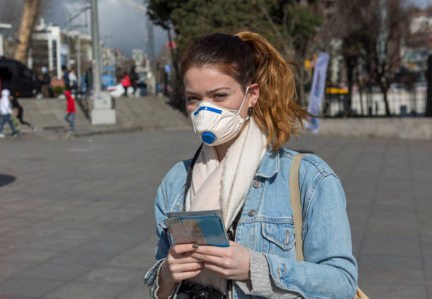 İstanbul Boğazı yakınlarında belediye tarafından yapılan sevgililer günü süslemeleri ile Beşiktaş plaza merkezinde yüz maskeli genç kız stok fotoğrafı