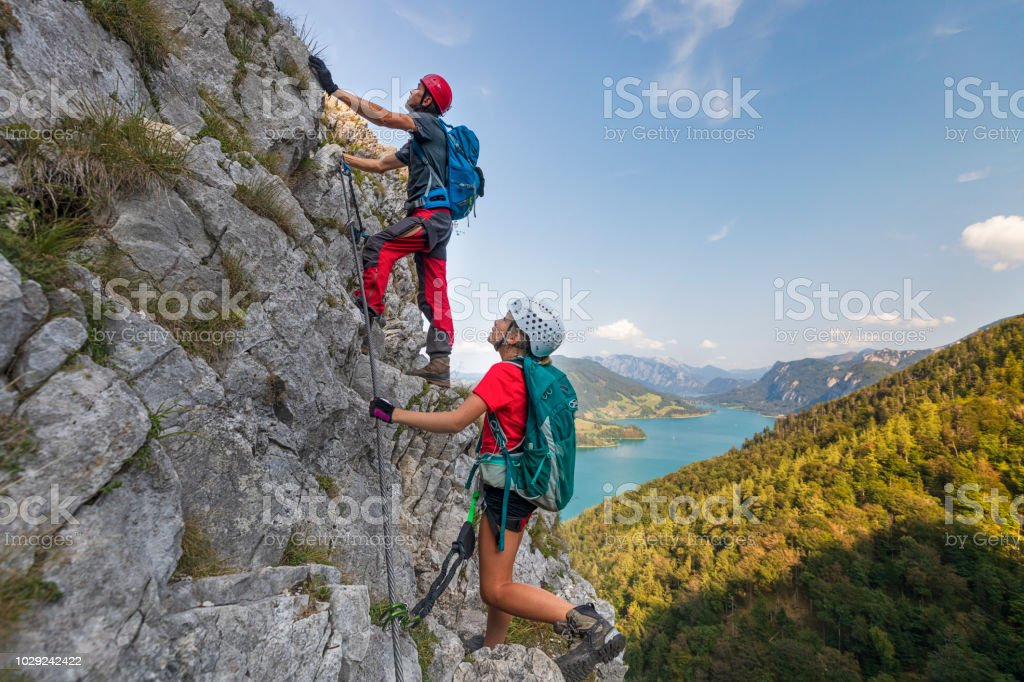 Young girl with Father is climbing to the top of a mountain in Alps stock photo