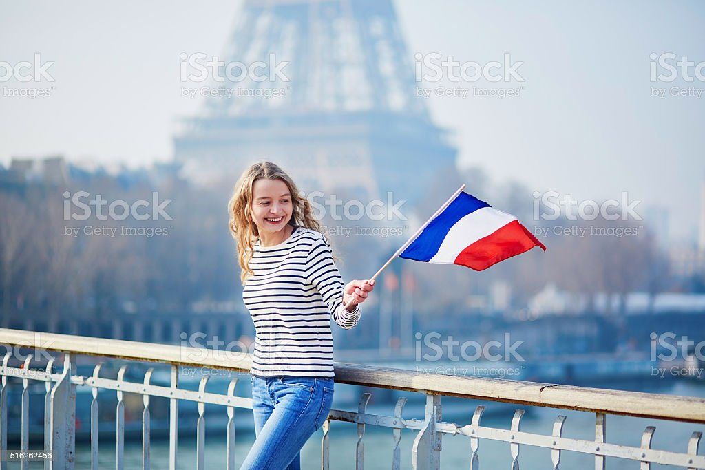 Young girl with French national flag near the Eiffel tower stock photo