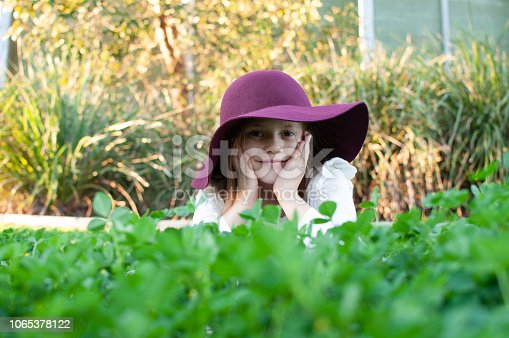Young girl with ginger hair in clover field wearing maroon wine hat and white t-shirt looking for four leaf clovers and smiling in Queensland Australia. St Patricks Day, St Patty's Day