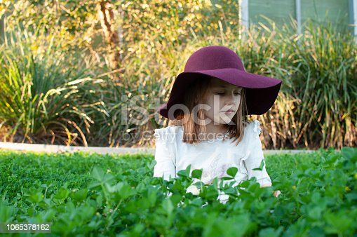 Young girl with ginger hair in clover field wearing maroon wine hat and white t-shirt looking for four leaf clovers and smiling in Queensland Australia, St Patrick's Day, St Patty's Day