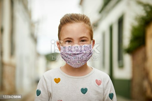 Portrait of young girl with home made face mask for coronavirus pandemic. Girl standing on the street with face mask.