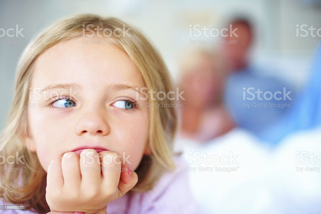 Young girl with hand on chin and parents in background royalty-free stock photo