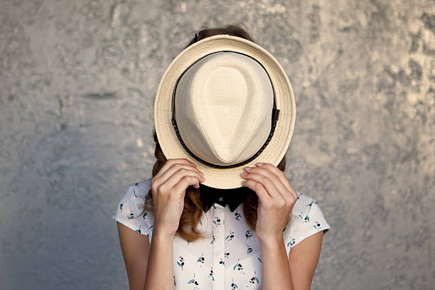Young girl with hat. Hides her face.Depression. The abstract image of leaving of the person from problems in the modern world. embarrassment stock pictures, royalty-free photos & images
