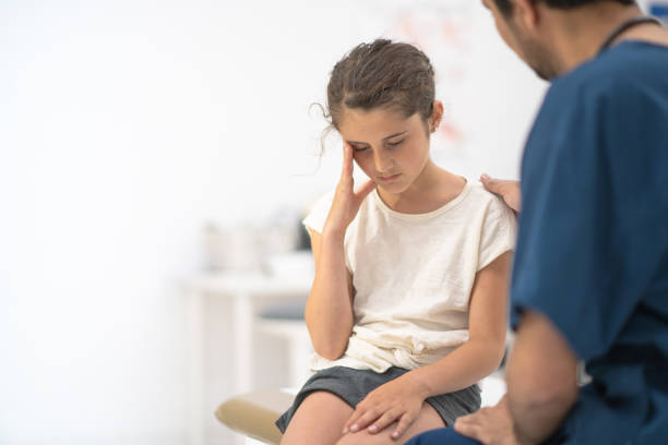 Young girl with headache in the doctor's office stock photo