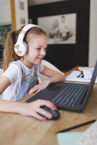 young girl with headphones and notebook stock photo
