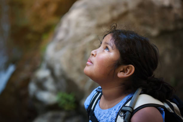 Young girl with hiking backpack looks up towards a difficult hiking trail ahead of her. stock photo