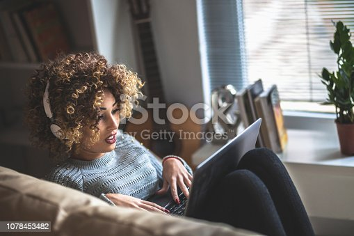 Young girl with laptop sitting in  living room