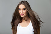 Young Girl with Long Flying Hair Posing over Grey Studio Background