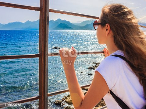 istock Young girl with long hair looks at the blue sea through the bars 1146620785