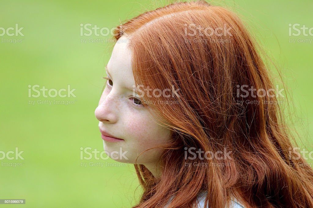 Young girl with long red hair smiling in garden, daydreaming stock photo