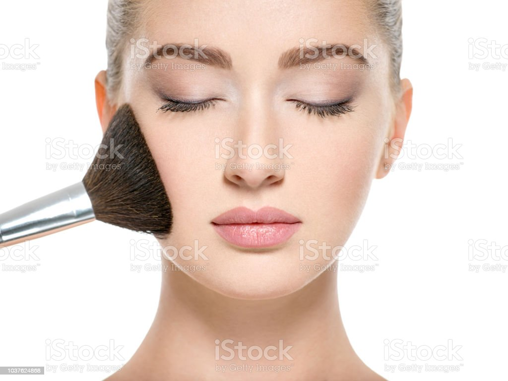Young girl  with makeup brush near at face stock photo