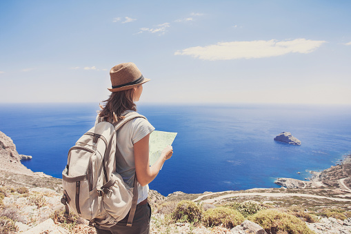 Young girl with map looking at the sea, travel concept