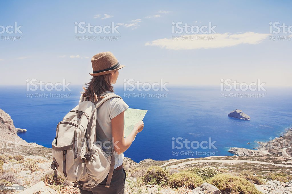 Young girl with map looking at the sea, travel concept stock photo