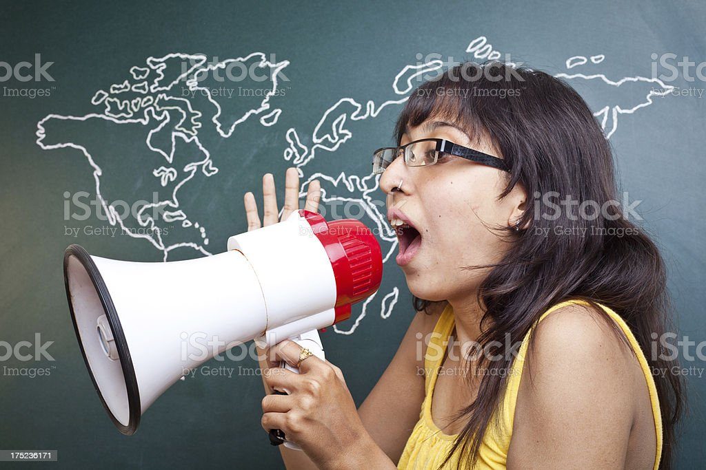 Young Girl with Megaphone annoucing in front of World Map royalty-free stock photo