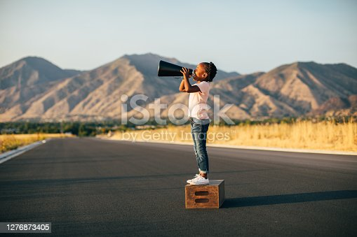 A young retro girl stands on a wooden box while yelling through a megaphone to have her message heard. Image taken in Utah, USA.