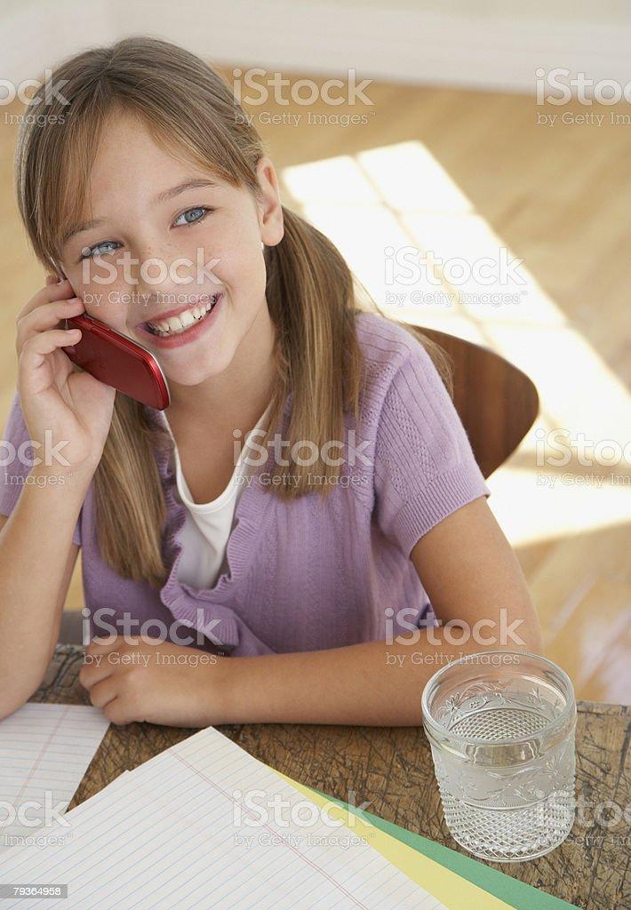 소녀, 모바일 전화 및 홈워크 주방에서 표 royalty-free 스톡 사진