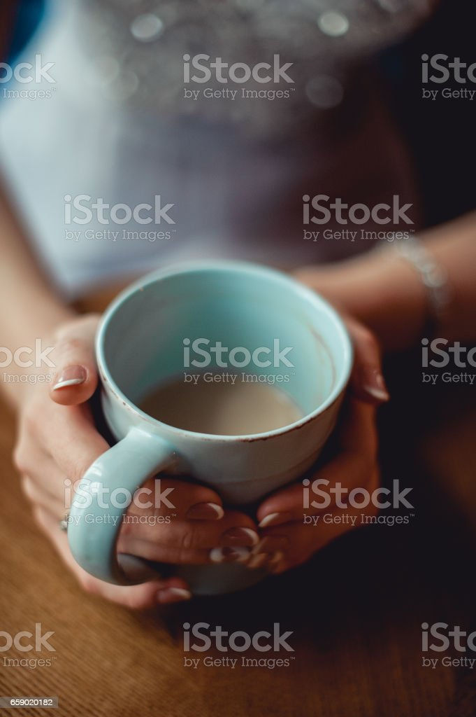 young girl with nice hands with white French manicure holding a blue vintage cup of coffee royalty-free stock photo