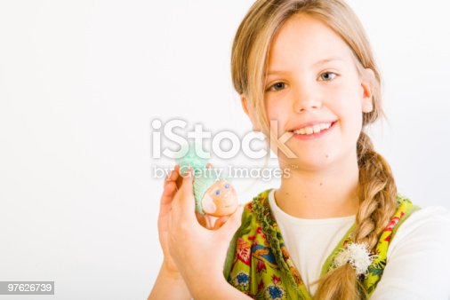 istock Young girl with painted egg and hat 97626739