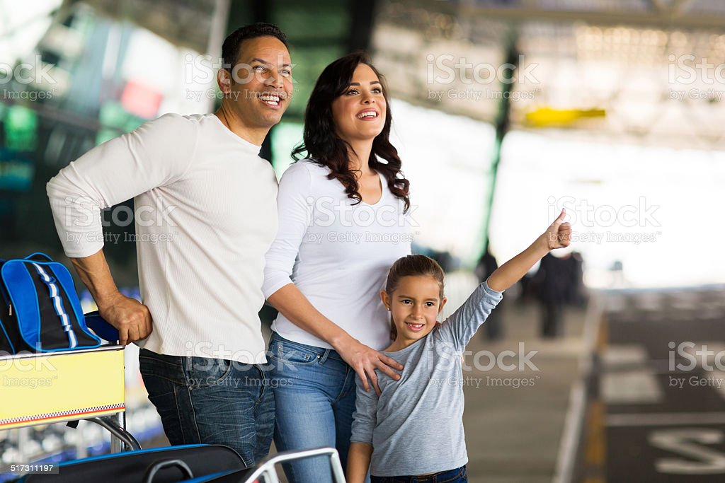 young girl with parents hailing taxi stock photo