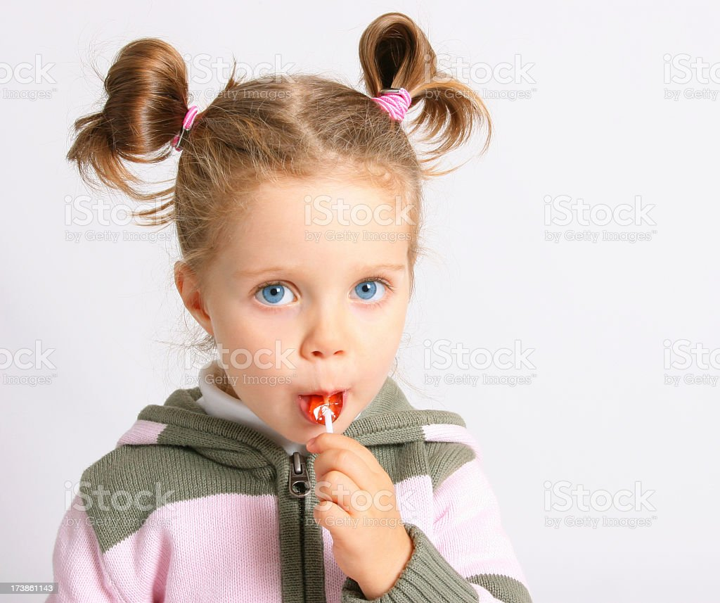 Young girl with pigtails sucking on a lollipop stock photo