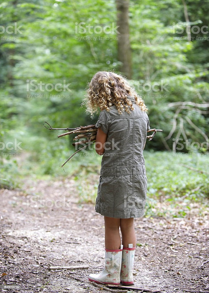 Young girl with pile of twigs in woods royalty-free stock photo