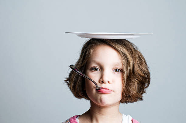 Young girl with plate on top of her head and spoon in mouth stock photo