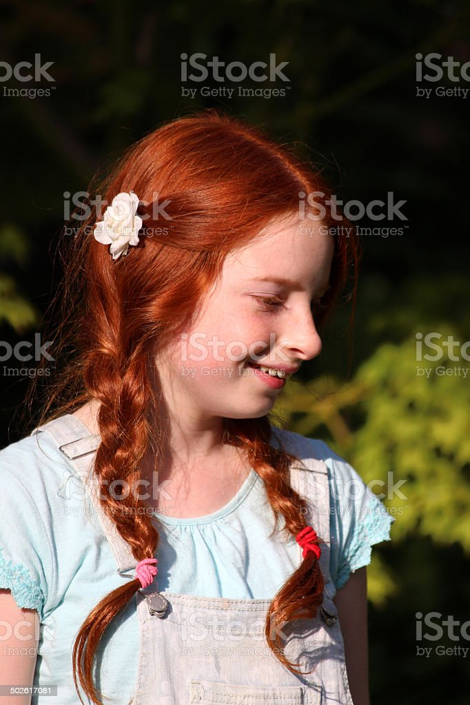 Young girl with red hair, long pigtails, plaits, braided hair stock photo