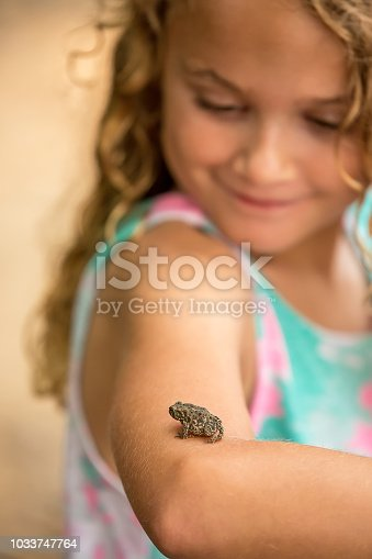 Focus is on the small toad resting on the girl's arm. The girl is smiling at the toad. Her face is not in focus. Taken on the bank of the Mississippi River on a summer day.