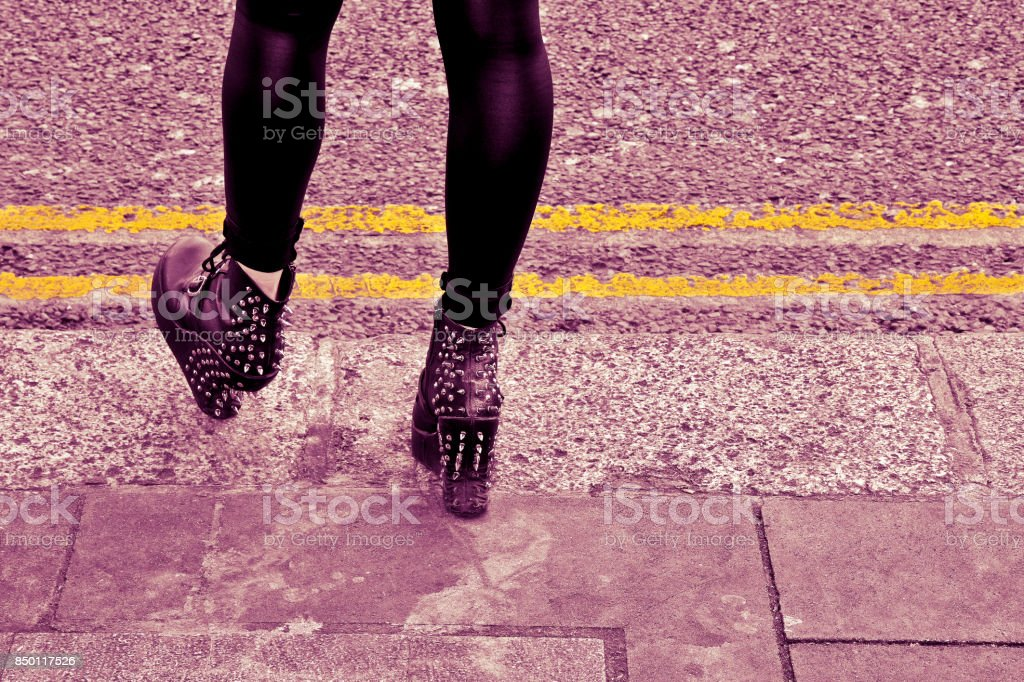 Young girl with spiked shoes waiting behind a yellow strip - concept image with copy space stock photo