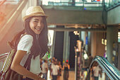 Young girl with suitcase down the escalator.Travel concept.