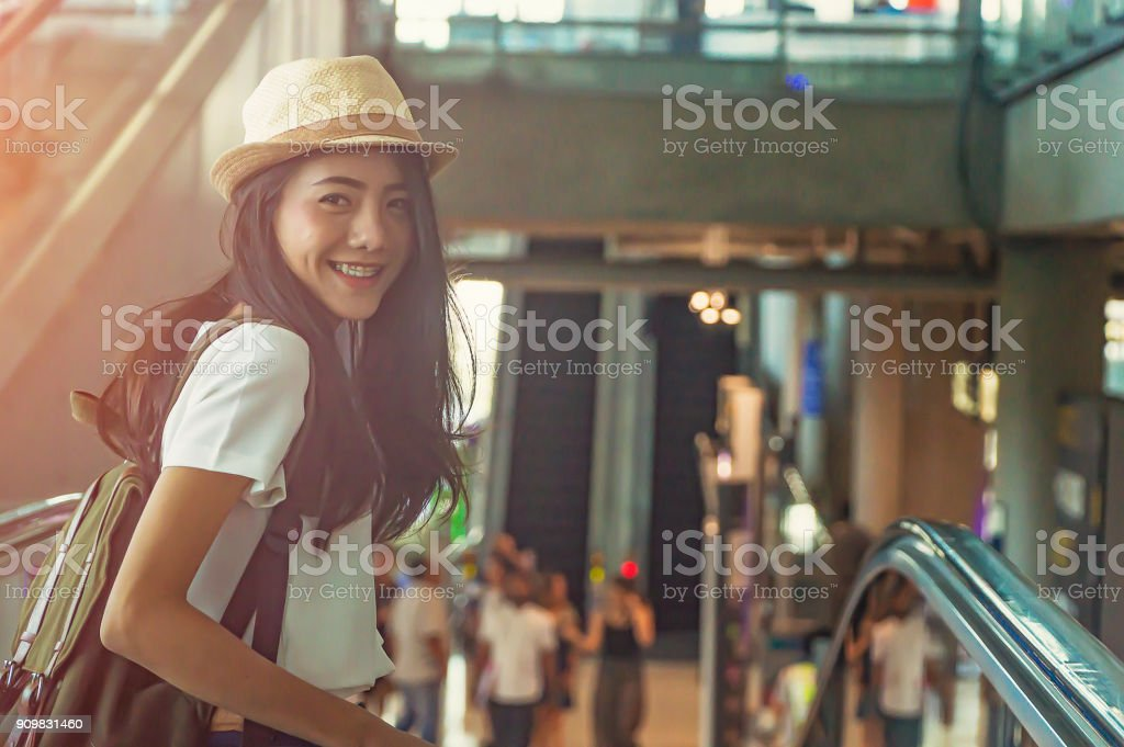 Young girl with suitcase down the escalator.Travel concept. stock photo