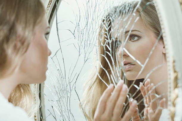 Young girl with teenage problems Young pretty girl with teenage problems looking in the broken mirror low self esteem stock pictures, royalty-free photos & images