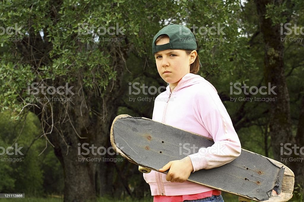 Young girl with well used skateboard stock photo