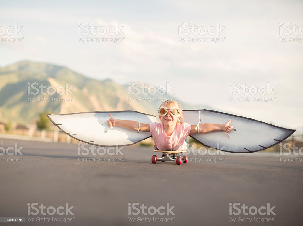 Young Girl with Wings Flies On Skateboard stock photo
