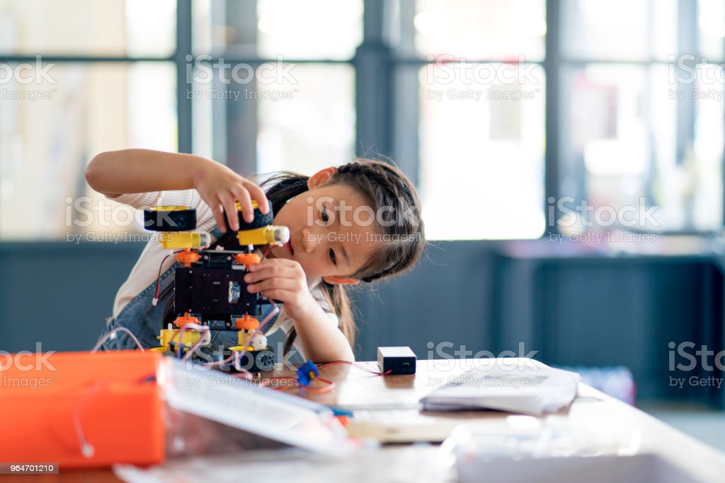 Young girl working on a robot design stock photo