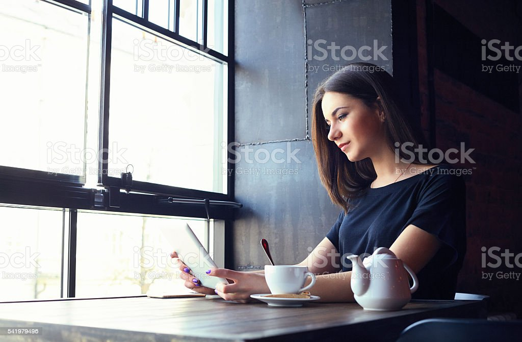 Young girl working on tablet computer in coffee shop stock photo
