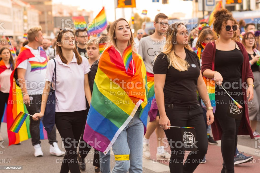 Young girl wrapped in rainbow flag marching along at the parade stock photo