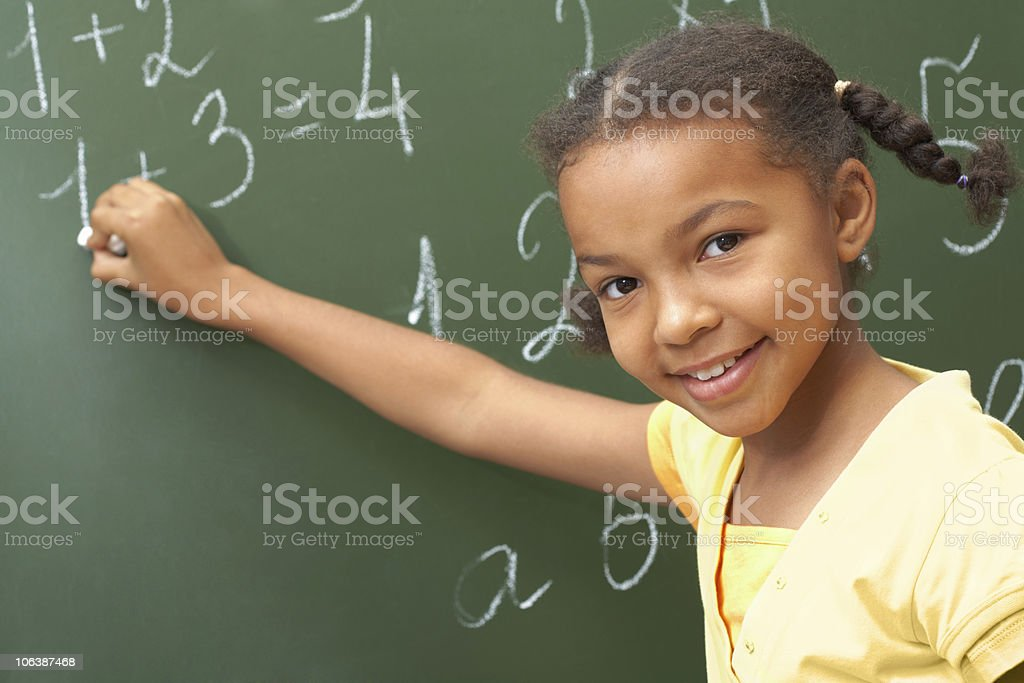 A young girl writing on a chalkboard royalty-free stock photo