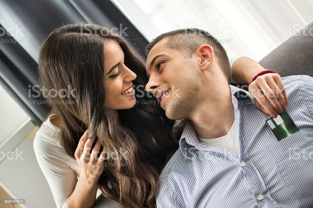 Young girlfriend stealing credit card from her boyfriend. stock photo