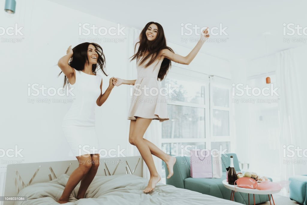Young Girls Are Jumping On Couch On The Hen-Party. stock photo