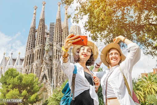 istock BARCELONA, SPAIN - 11 JULY 2018: Young girls friends making selfie photo on her smartphone in front of the famous Sagrada Familia catholic cathedral. Travel in Barcelona concept 1144739356