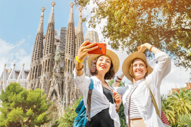 BARCELONA, SPAIN - 11 JULY 2018: Young girls friends making selfie photo on her smartphone in front of the famous Sagrada Familia catholic cathedral. Travel in Barcelona concept BARCELONA, SPAIN - 11 JULY 2018: Young girls friends making selfie photo on her smartphone in front of the famous Sagrada Familia catholic cathedral. Travel in Barcelona concept barcelona spain stock pictures, royalty-free photos & images