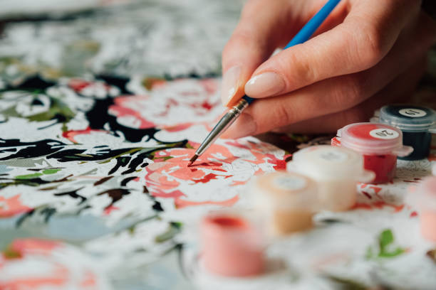 Young girl's hand draws with a brush painting by numbers on canvas. Creative hobby. Leisure activity at home during self-isolation COVID-19