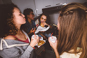 Happy multi-ethnic friends and roommates having fun at college dorm party eating fast food