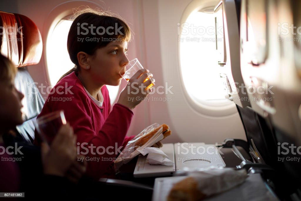 Young girls having meal on board of plane stock photo