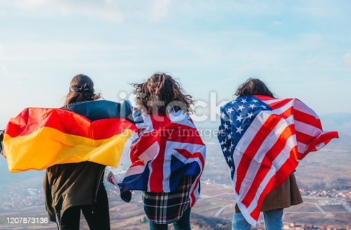Young girls hold flags: America, Germany and Great Britain. Student exchange.