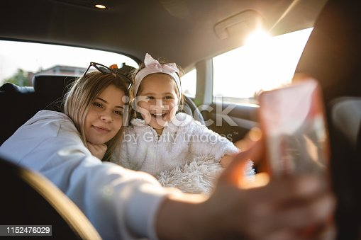 807410214istockphoto Young girls in a car taking selfie with smartphone 1152476029